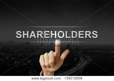 business hand clicking shareholders button on black blurred background