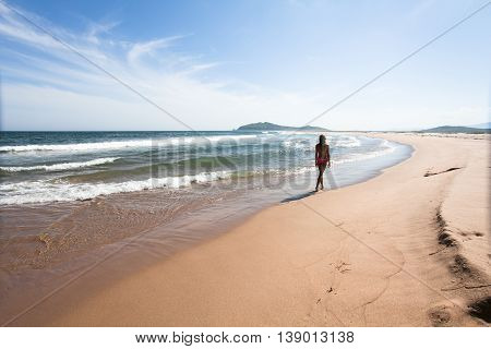 Young woman walking through the empty wild beach against a blue sky yellow sand and sea. Wide angle.