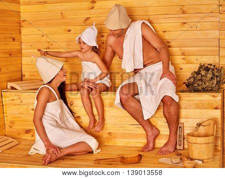 Happy family with child in hat relaxing at sauna. Sauna for healthy