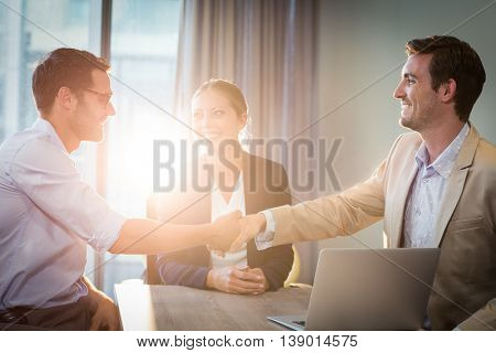 Businessman shaking hands with coworker in the office