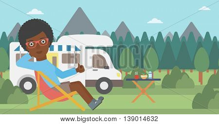 An african-american woman sitting in folding chair and giving thumb up on the background of camper van. Woman enjoying vacation in camper van. Vector flat design illustration. Horizontal layout.