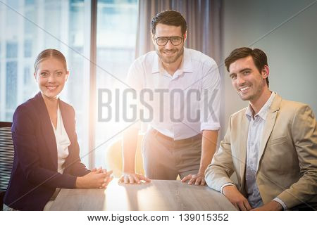 Portrait of businessmen and businesswoman sitting at their desk in the office