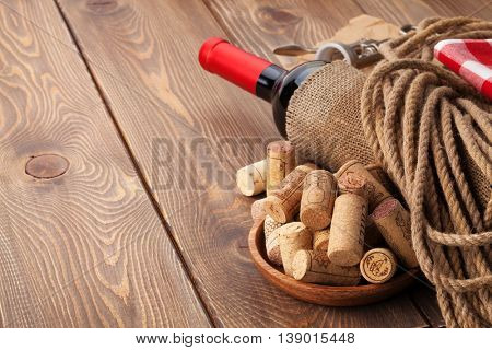 Red wine bottle, corks and corkscrew over wooden table background with copy space