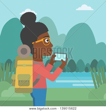 An african-american woman taking photo of landscape with mountains. Young hiking woman with backpack taking photo with her cellphone. Vector flat design illustration. Square layout.
