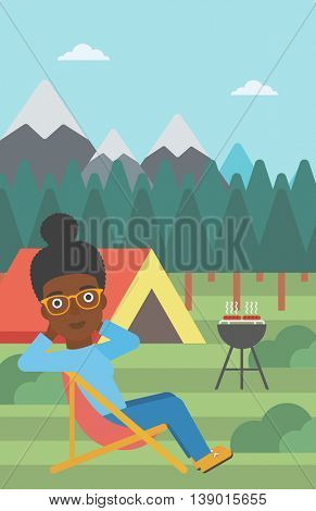 An african-american woman sitting in a folding chair in the camp. Travelling woman relaxing and enjoying her camping holiday near the tent. Vector flat design illustration. Vertical layout.
