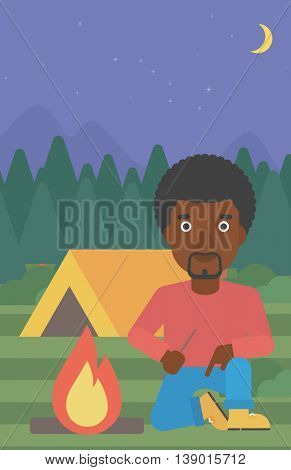 An african-american man kindling a campfire on the background of camping site with tent. Tourist relaxing near campfire. Vector flat design illustration. Vertical layout.