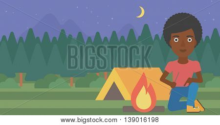 African-american woman kindling campfire on the background of camping site with tent. Tourist relaxing near campfire. Woman sitting near campfire. Vector flat design illustration. Horizontal layout.