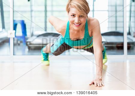 Frontal view of smiling young woman doing one arm pushup in gym