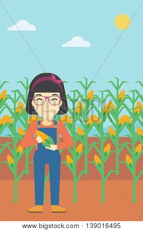 An asian female farmer holding a corn cob. Young farmer standing on the background of corn field. Vector flat design illustration. Vertical layout.