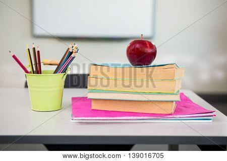 Close-up of apple with books and desk organizer on table in classroom