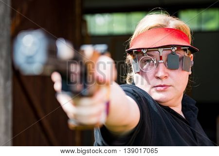 Woman concentrating on sport shooting training, horizontal