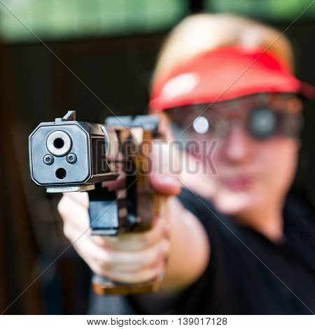 Woman concentrating on sport shooting training, square image