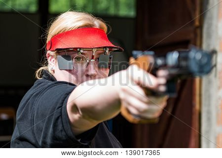 Woman concentrating on sport shooting training, horizontal image