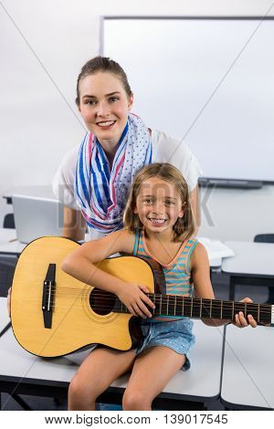 Portrait of young teacher assisting girl to play guitar in classroom