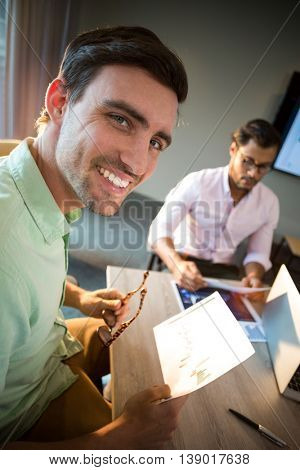 Close-Up of man smiling at camera while his colleague reading document in the background
