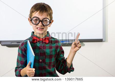 Portrait of boy raising hand against whiteboard in classroom