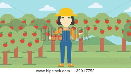 An asian female farmer holding a box with apples in one hand and an apple in another on a background of garden with trees. Farmer collecting apples. Vector flat design illustration. Horizontal layout.