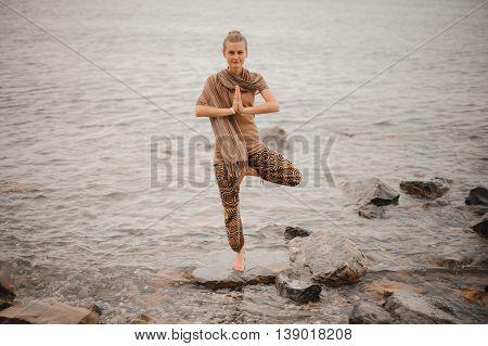 Woman doing a yoga tree pose namaste on the stone near the ocean