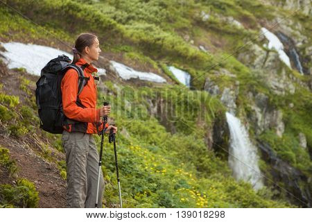 Young woman with backpack stands in outdoor nature scenery during summer sunny day.