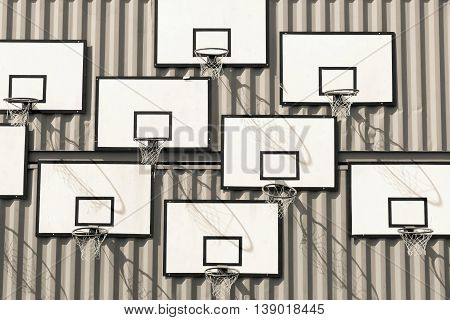 the abstract composition of group of basketball baskets of tone sepia of beige color with rectangular boards is located on a wall of iron containers