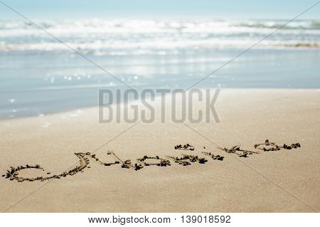 The inscription on the sand seashore. The name is written on the wet sand of the sea.