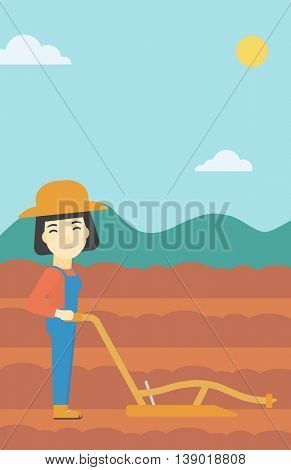 An asian female farmer using a plough on the background of plowed agricultural field. Farmer working with a plough. Vector flat design illustration. Vertical layout.