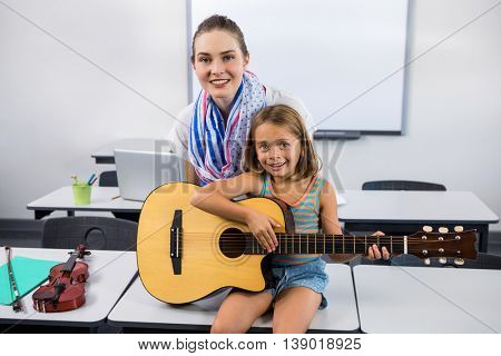 Portrait of teacher assisting girl to play guitar against whiteboard in classroom