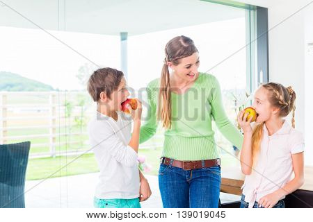 Mother giving children fresh fruits for healthy living