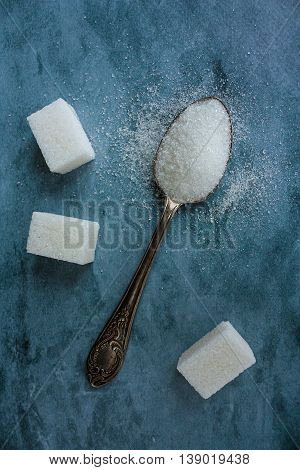 Spoon full of granulated sugar. Sugar pieces