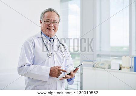 Portrait of smiling Vietnamese doctor working in hospital