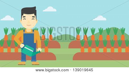 An asian farmer holding a watering can. Farmer watering carrots. Farmer standing on the background of carrots growing on field. Horizontal layout.