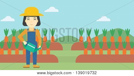 An asian female farmer holding a watering can. Farmer watering carrots. Female farmer standing on the background of carrots growing on field. Horizontal layout.
