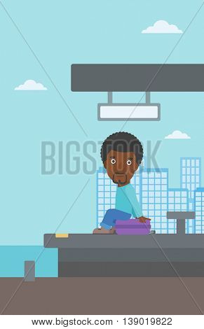 An african-american young man sitting on a suitcase at the train station. Young man waiting for a train at the railway platform. Vector flat design illustration. Vertical layout.