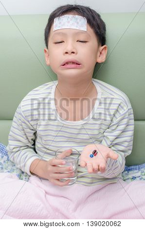 Young Asian boy don't want to eat medicine pills