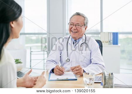 Cheerful mature doctor giving advice to female patient