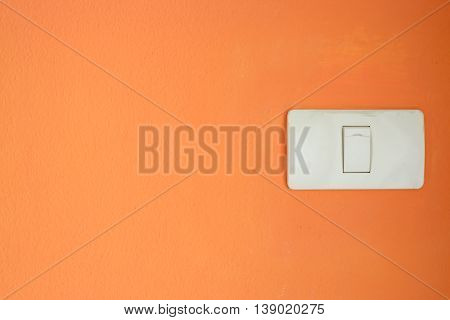 White light switch turn on or turn off the lights on orange wall.