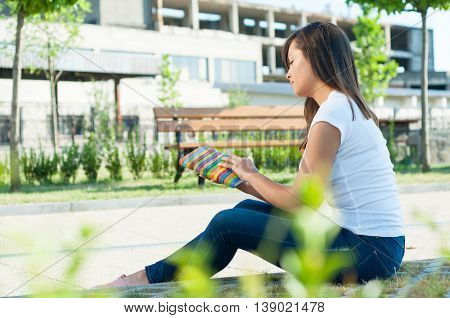 Attractive Girl Holding Agenda Or Notebook Outside In Park