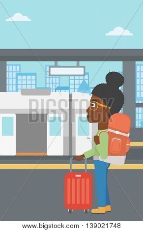 An african-american woman standing at the train station on the background of train with open doors. Young woman with suitcase waiting for a train. Vector flat design illustration. Vertical layout.