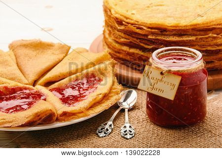 Stack of gluten free pancakes made from corn flour served with raspberry jam.