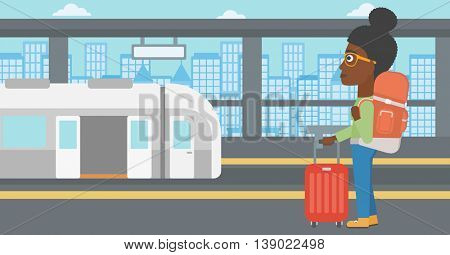 An african-american woman standing at the train station on the background of train with open doors. Young woman with suitcase waiting for a train. Vector flat design illustration. Horizontal layout.