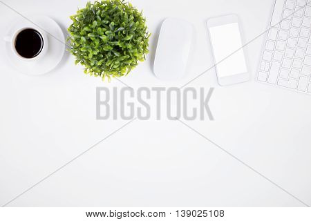 Top view of bright office desktop with blank white mobile phone computer mouse keyboard coffee cup and decorative plant. Mock up