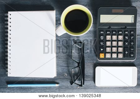 Top view of wooden office desktop with blank white mobile phone spiral notepad coffee mug glasses blue pencil and calculator. Closeup Mock up