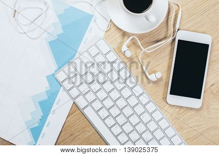 Wooden office table with blank smartphone and headphones keypad business report and coffee cup. Top view Closeup Mock up