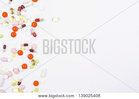 White surface with colorful pills and capsules on the left. Mock up