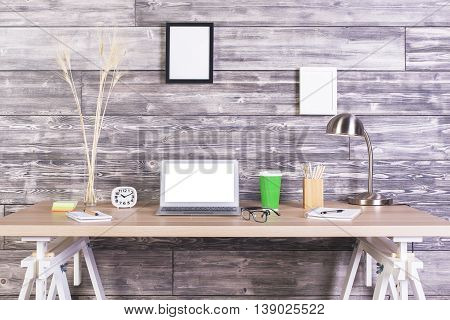 Creative designer tabletop with blank white laptop clock coffee and other items with picture frames hanging above on wooden wall. Mock up