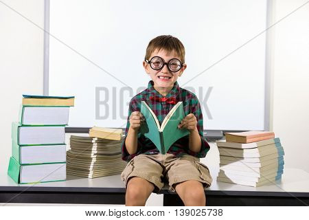 Portait of boy holding book while sitting on table in classroom