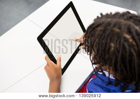 High angle view of boy using digital tablet in classroom