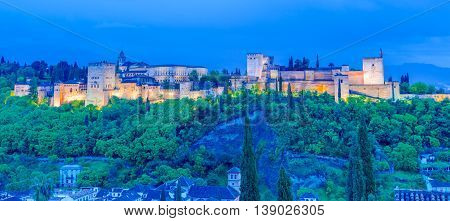 Panoramic view of Alhambra palace on the hill, illuminated at night in Granada - Andalusia, Spain
