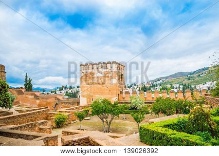 Wide view of a garden and beautiful tower architecture inside Alhambra Palace, Cordoba - Spain