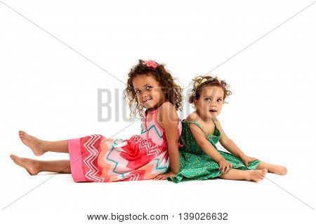 Mulatto sisters are sitting back to back playing. Girls in red and green dress are playing smiling and showing sister love and happiness. A girl is missing one tooth. Isolated on white background.